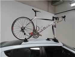 Roof mounted bicycle carrier with vacuum cups mounted on car